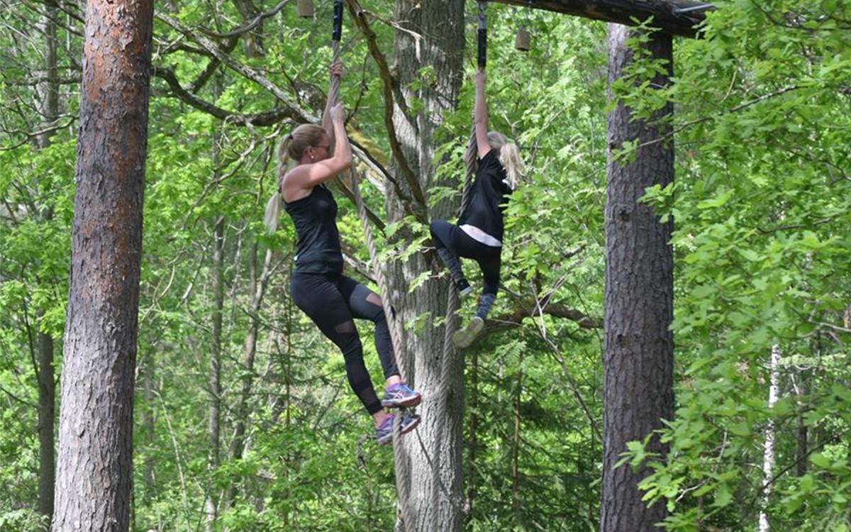 Kvinna och barn som klättrar på OCR banan.